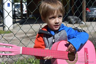 Kind mit Gitarre im Garten